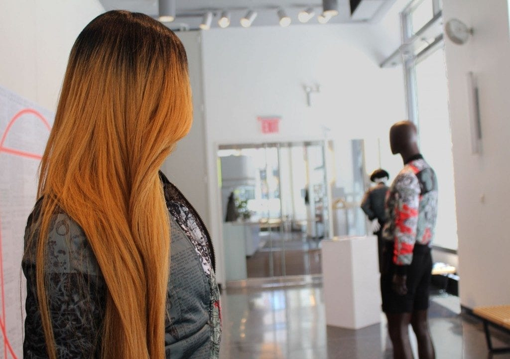 Gallery space: mannequin with ombre wig and bomber jacket displayed.