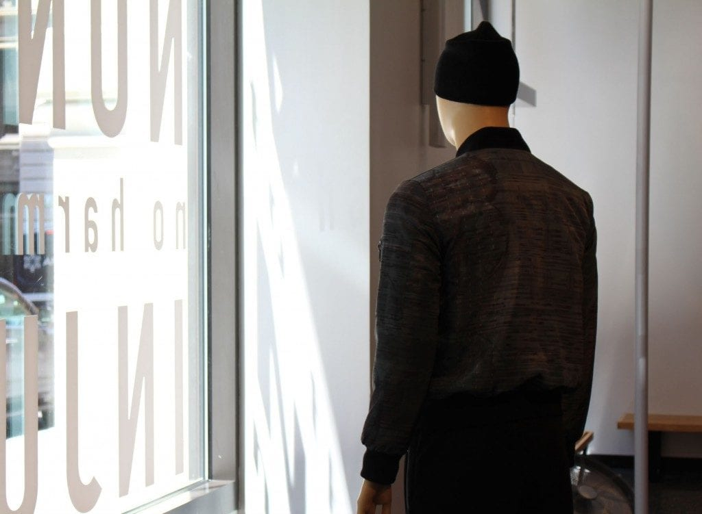 Gallery space: mannequin in black bomber and black beanie