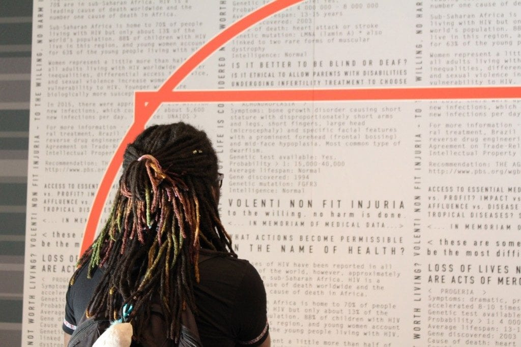 Gallery goer with dreads analyzing work on the wall