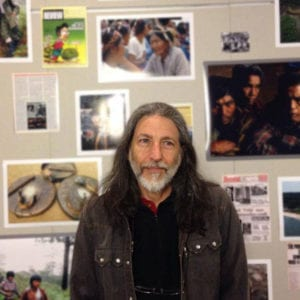 Man poses in front of gallery wall