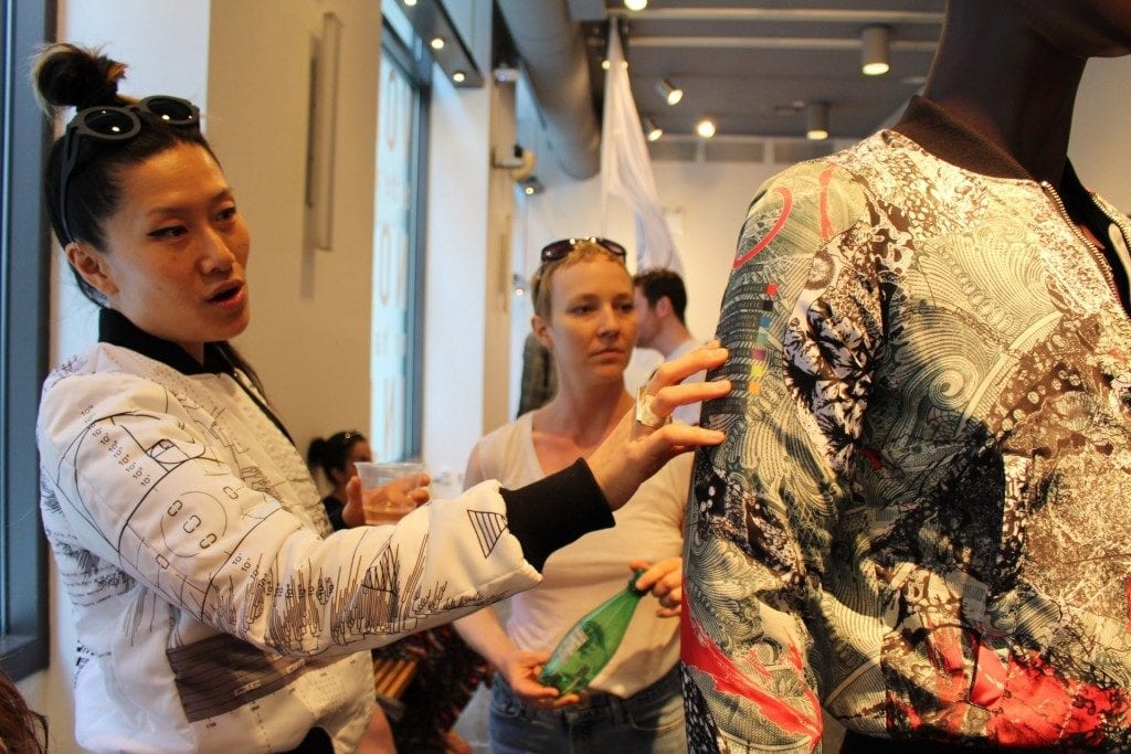 Action shot of artist showing the details of her mannequin's jacket