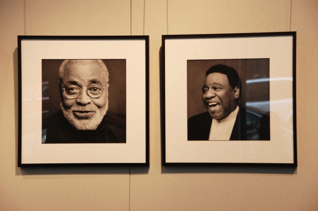 On gallery wall, two framed black and white portraits of famous black actor James Earl Jones and the other of musician Al Green.