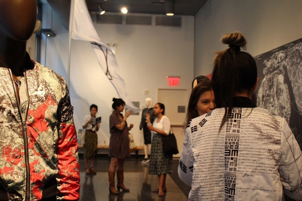 Gallery space: mannequin with designer jacket and several people talking in the space