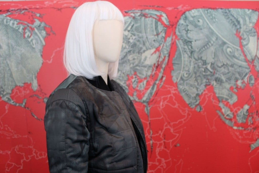 Mannequin with short white wig and black bomber jacket in front of red artwork.
