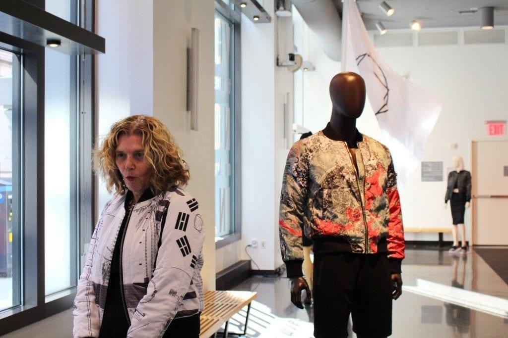 Woman in bomber jacket alongside mannequin in a similar jacket