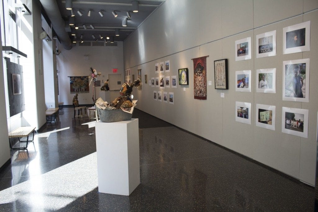Gallery space with african sculpture and prints on wall.