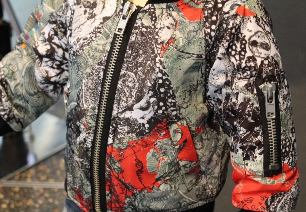 Detail shot of bomber jacket with graphic of dna and money collage.