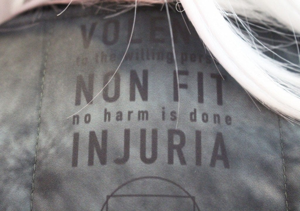"""Close up shot of jacket with text """" VOLEN to the willing NON FIT no harm is done INJURIA"""""""