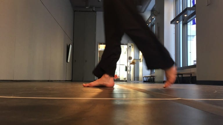 Feet walking in gallery space