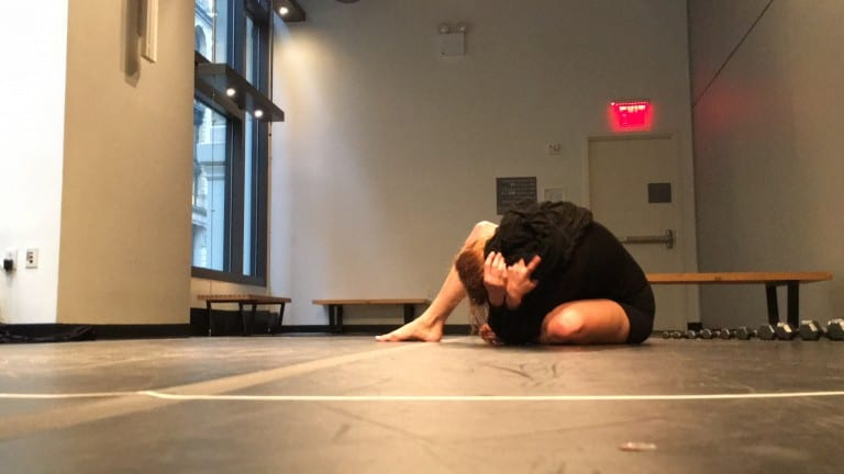 Woman on floor of gallery space, holding her head into her hands.