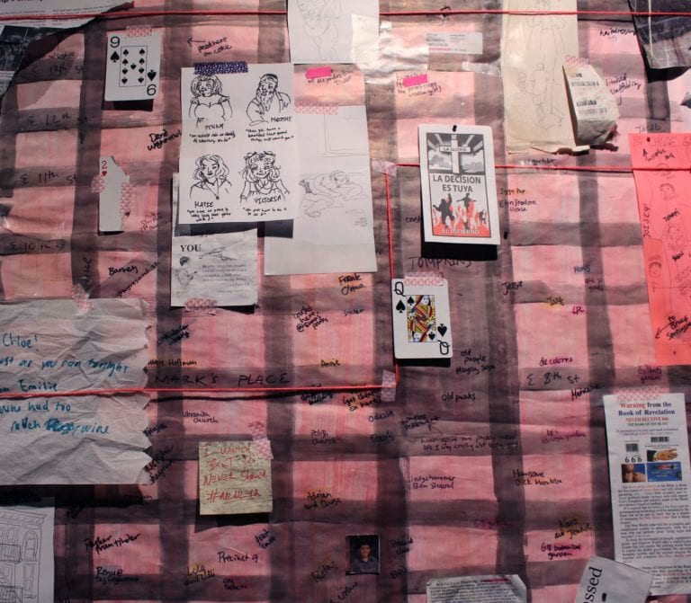 Sketches, paper, string and cards on quilt.