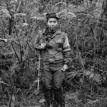 Black & White portrait of young woman soldier in a rain forest