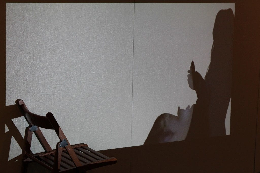 Projected shadow on Gallery wall with a chair.