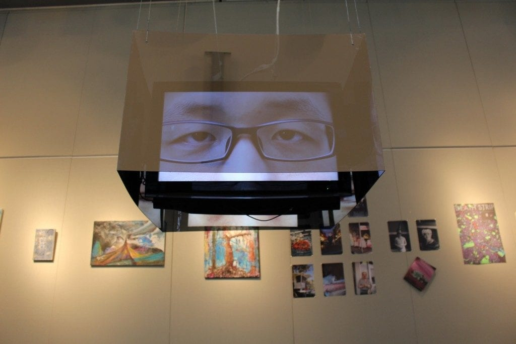 Gallery Space: monitor hanging from ceiling projecting eyes and prints/paintings on gallery wall.