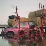 Pink car with bundles of hay placed in it's trunk and on it's roof, sinks in a lake.
