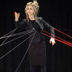 Woman performs in all black dress suit and with strings attached to her.