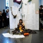 Woman sits amongst various documents and her coat while others surround her in gallery space