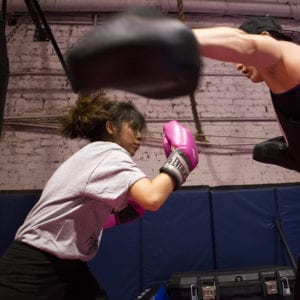 Action shot of young girl boxing with a woman.