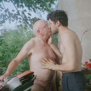 Older naked man kisses younger shirtless man