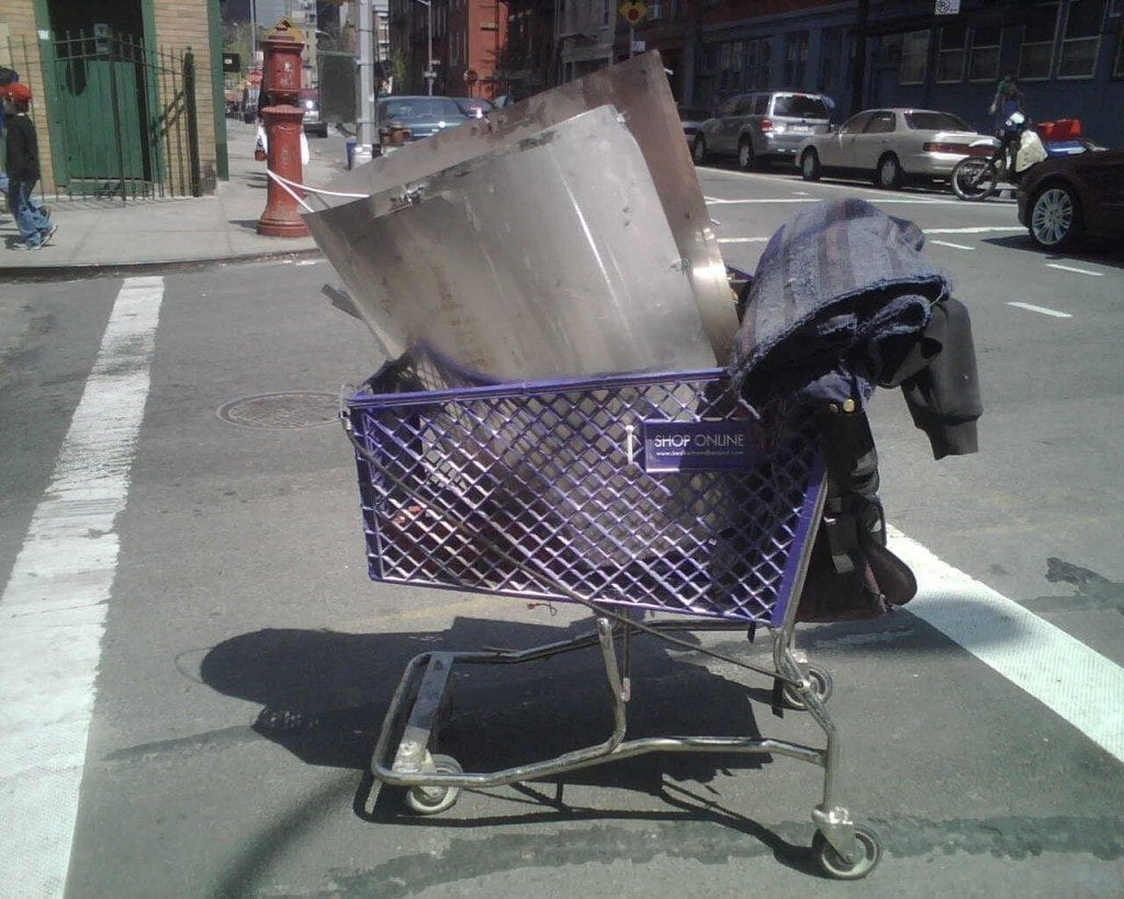 Portrait of shopping cart with abandoned items including a jacket, in the middle of a street.