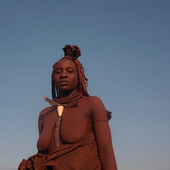 Himba Woman wearing red clay on body and hair.