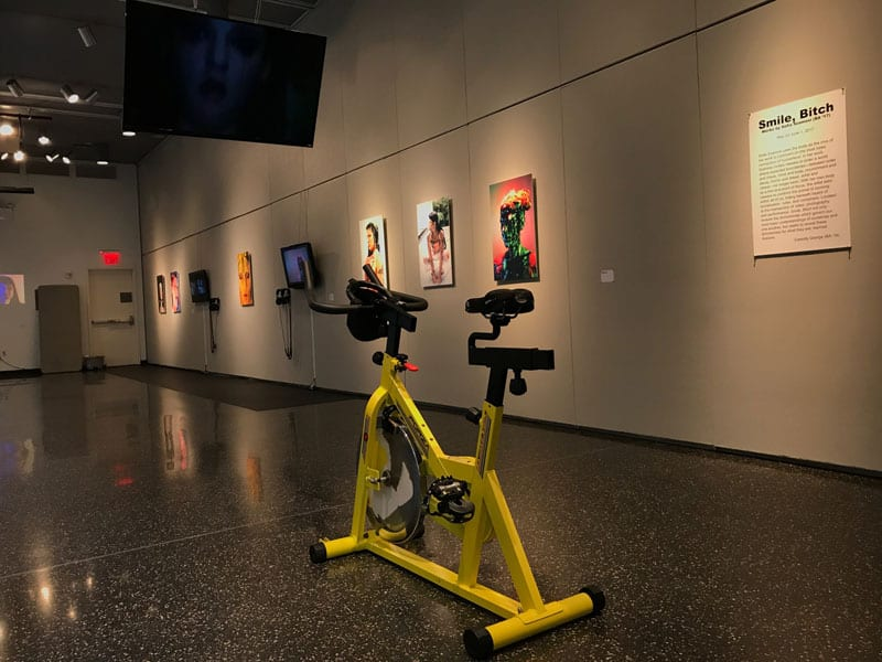 Stationary bike in gallery space with a monitor in front of it