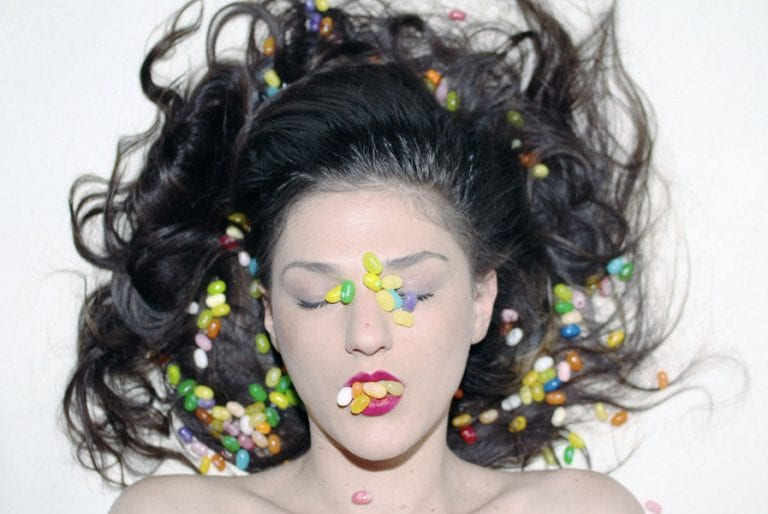 Woman with jelly beans on her face