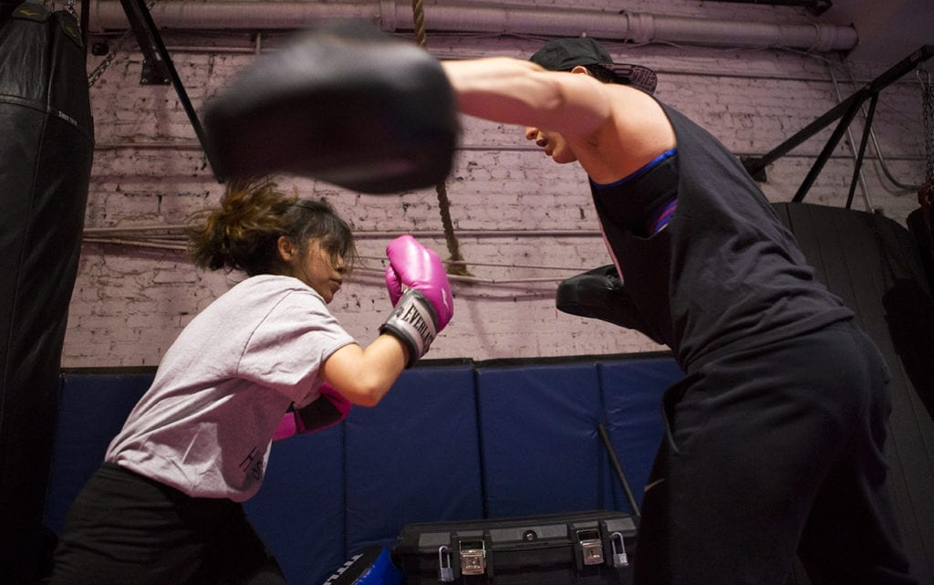 Action shot of two girls boxing.
