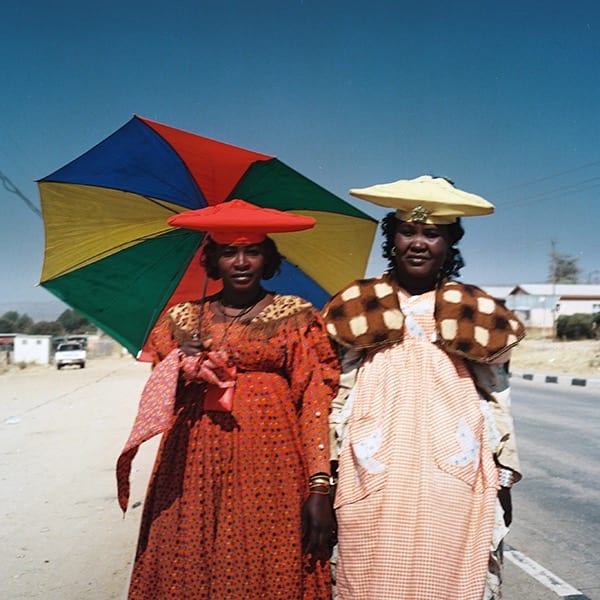Two Namibian women standing outside, woman on left holding a rainbow umbrella and wearing a red dress and hat. Woman on right in beige hat and pink and brown dress.