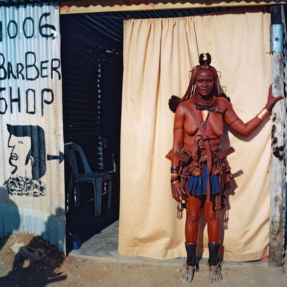 Namibian (Himba) woman with red clay on body and traditional clothing poses in front of a babershop.