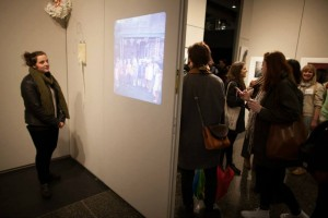 Video playing on left, people enjoying art work on right