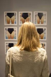 Woman looking at wall of artwork