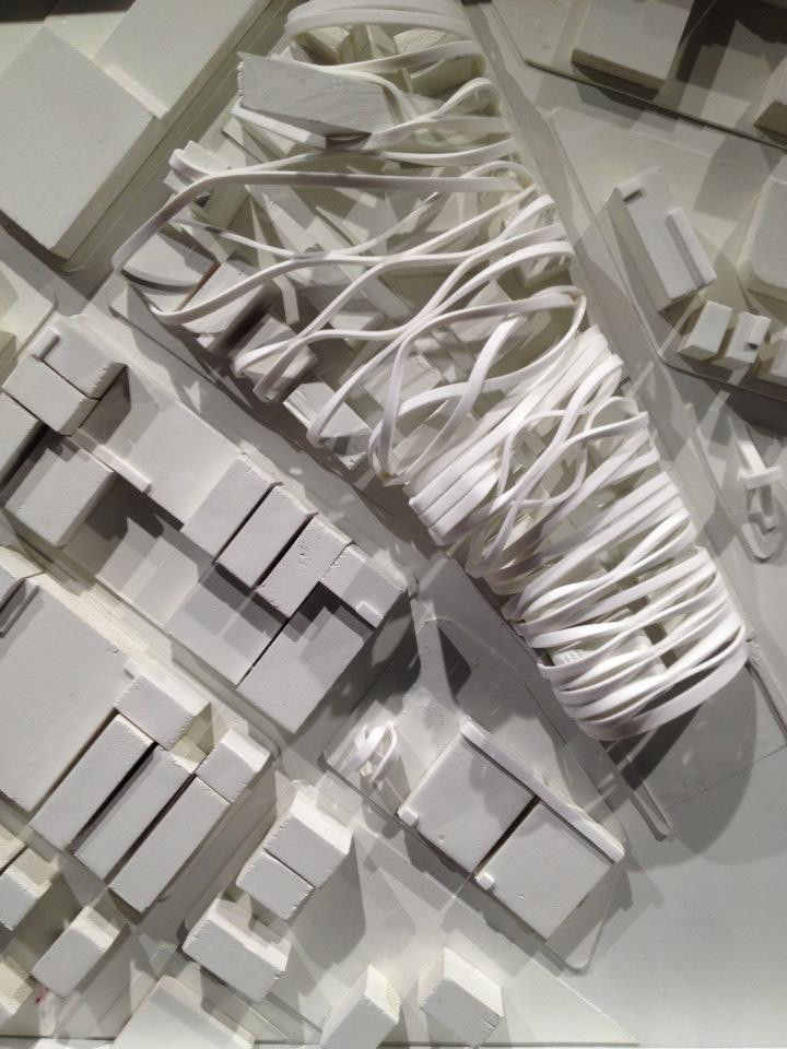 an architectural model on the centre of which is a white ribbon wrapped around a dissecting structure