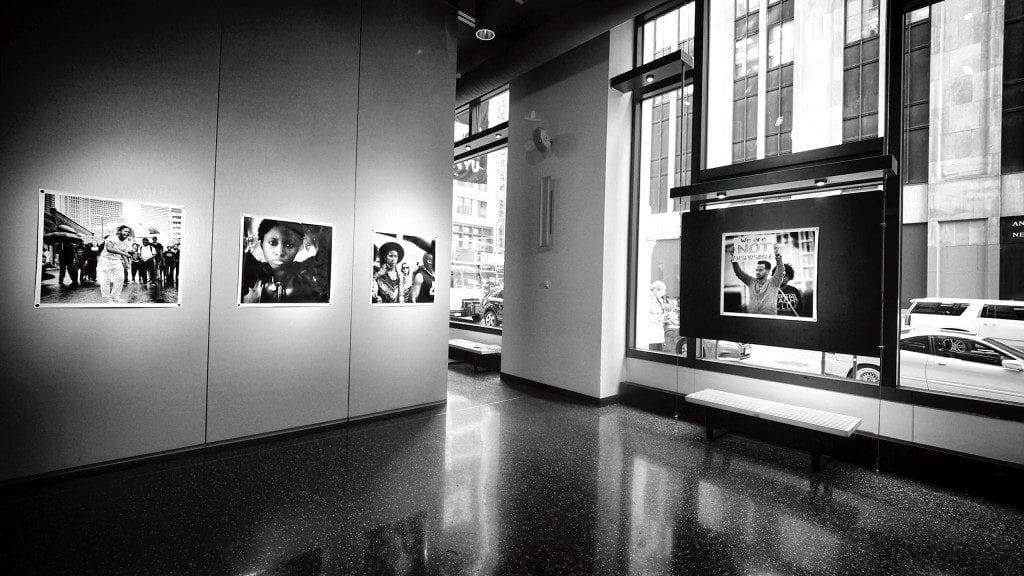 B&W photo of portrait collages in gallery