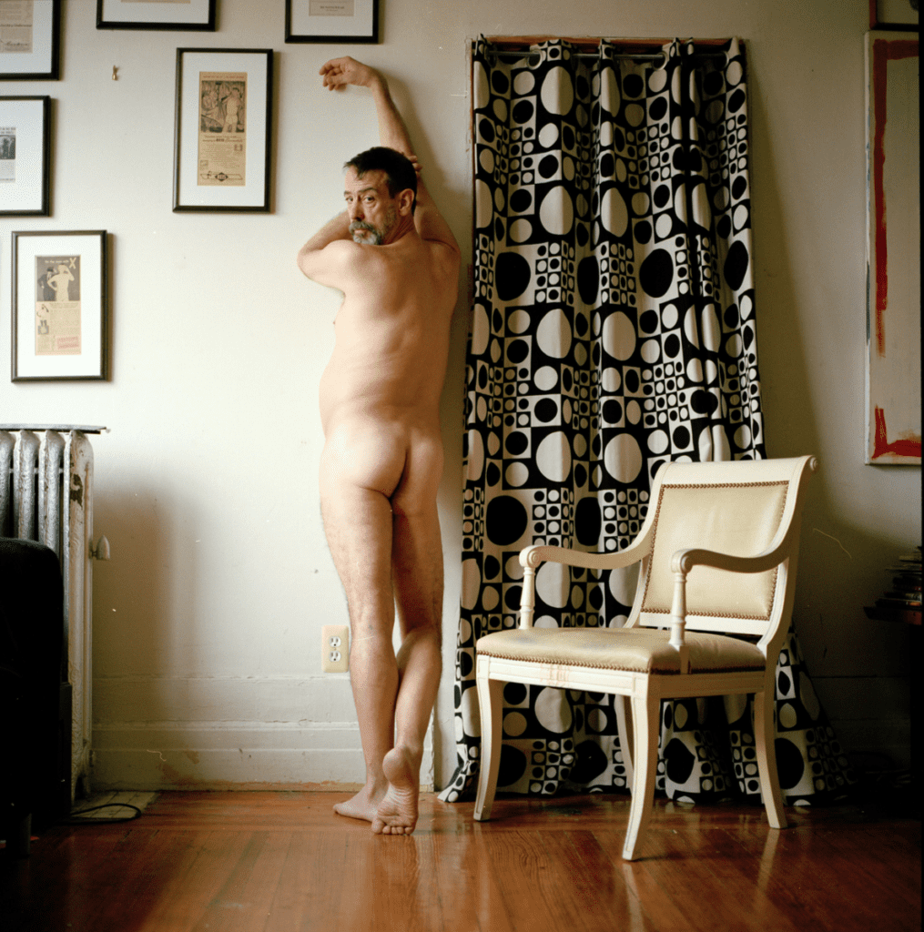 Naked man poses against wall