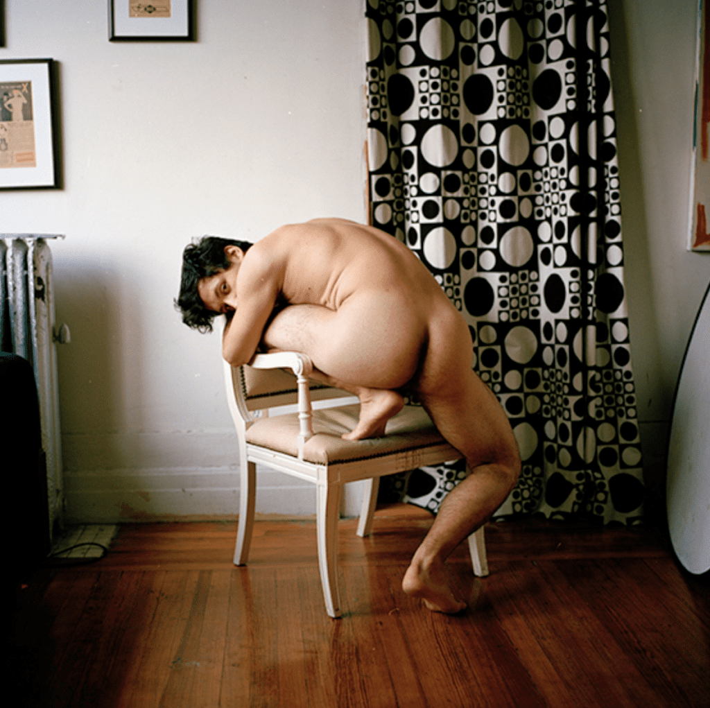 Naked man poses on a chair