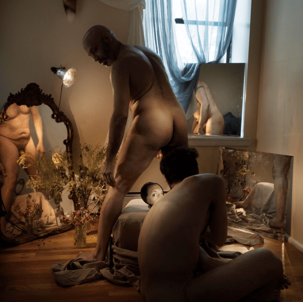 An older and younger man pose naked using mirrors
