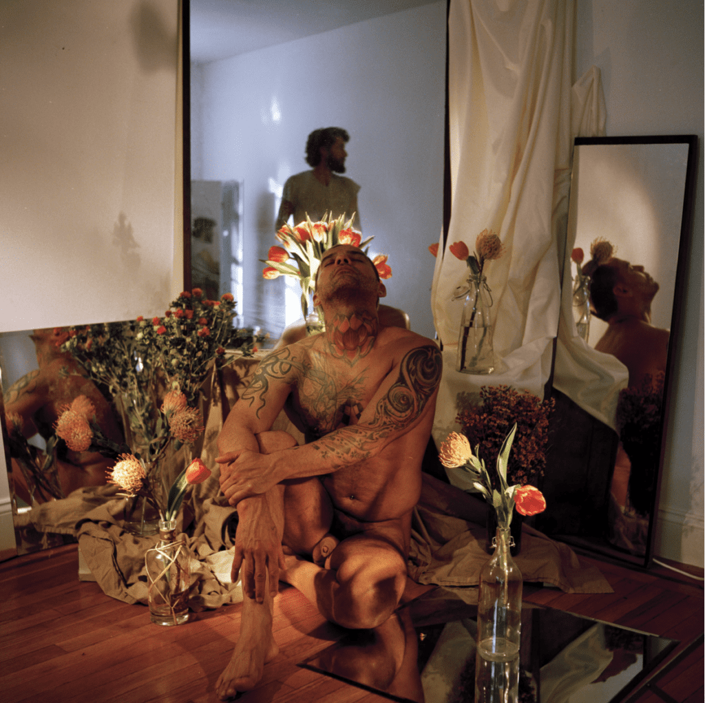 Naked man poses with flowers and mirrors