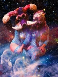 Two girls dressed as sea creatures in front of a galaxy background
