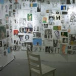 chair in room facing walls filled with pictures