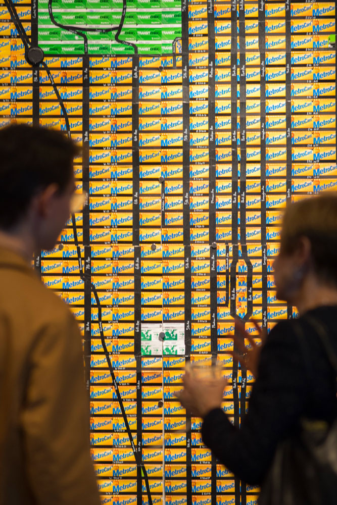 People looking at a wall of metrocards