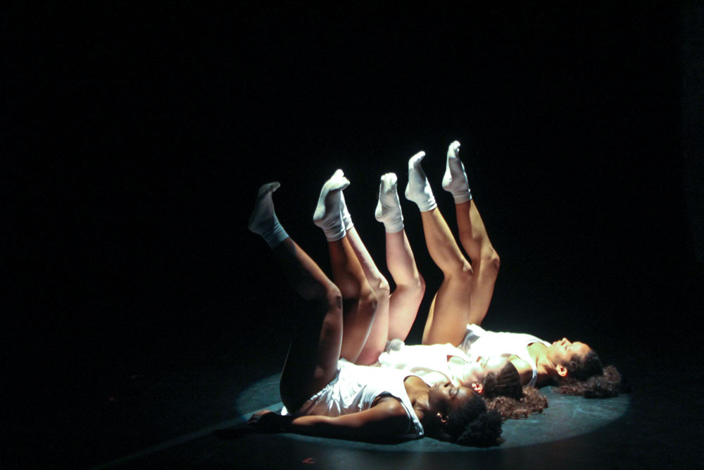 dancers laying on ground with legs in the air