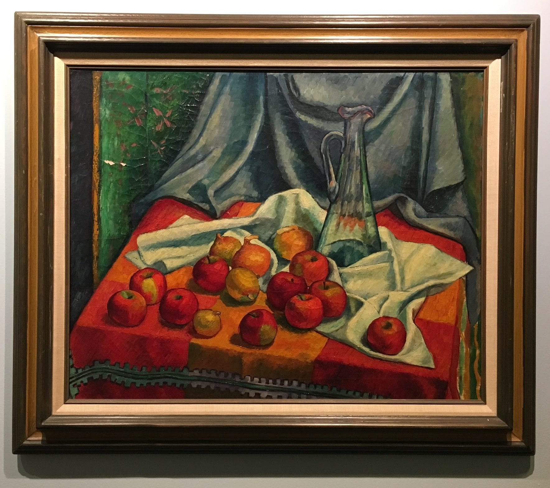 apples on a red table cloth by a blue curtain