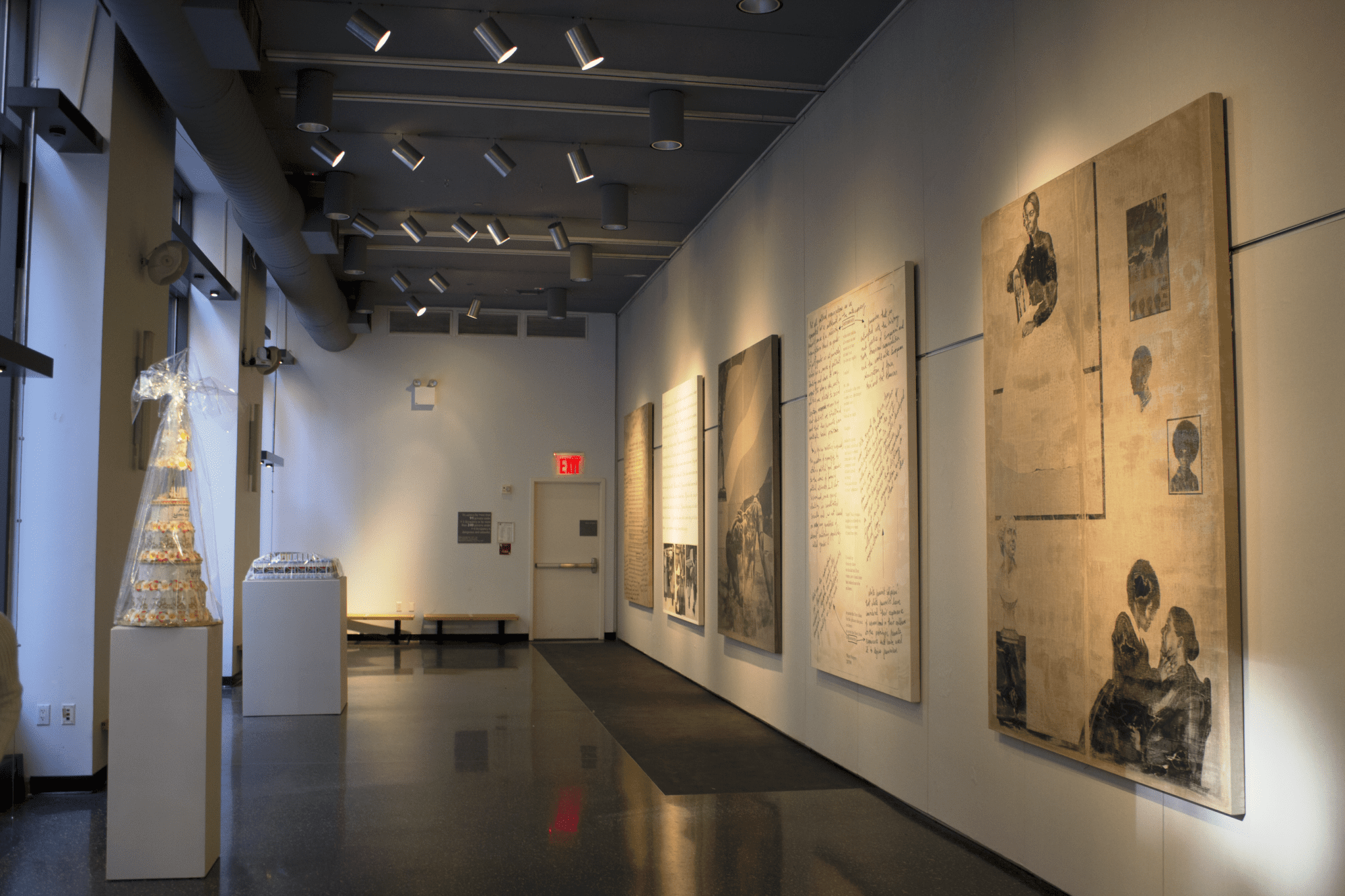 Photograph of a gallery space, the wall on the right has five large canvases hung on it, and the lefthand side has two pedestals with cake sculptures atop it.