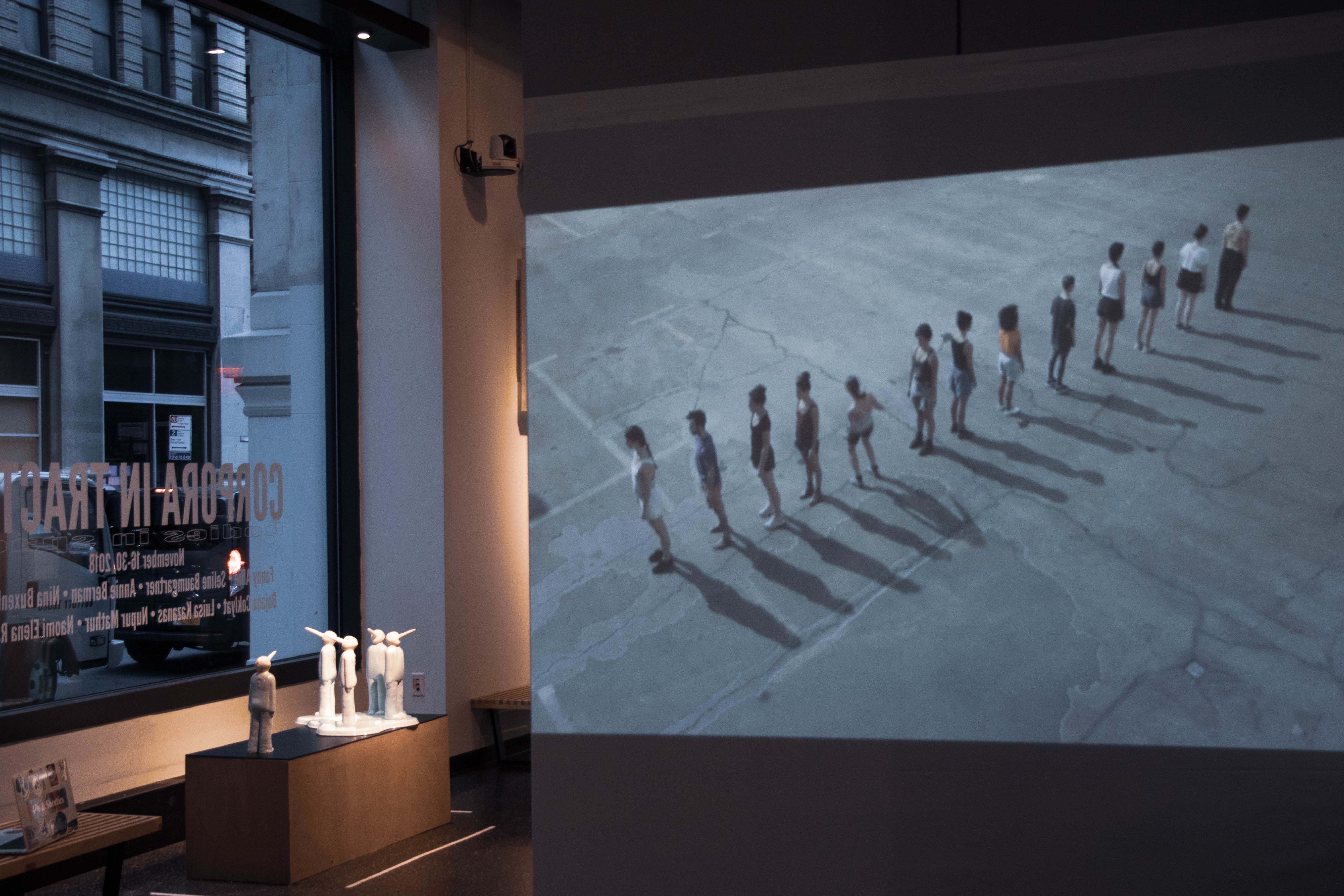 gallery shot with a video projection on the righthand side and an illuminated platform with sculptural figures on the left.