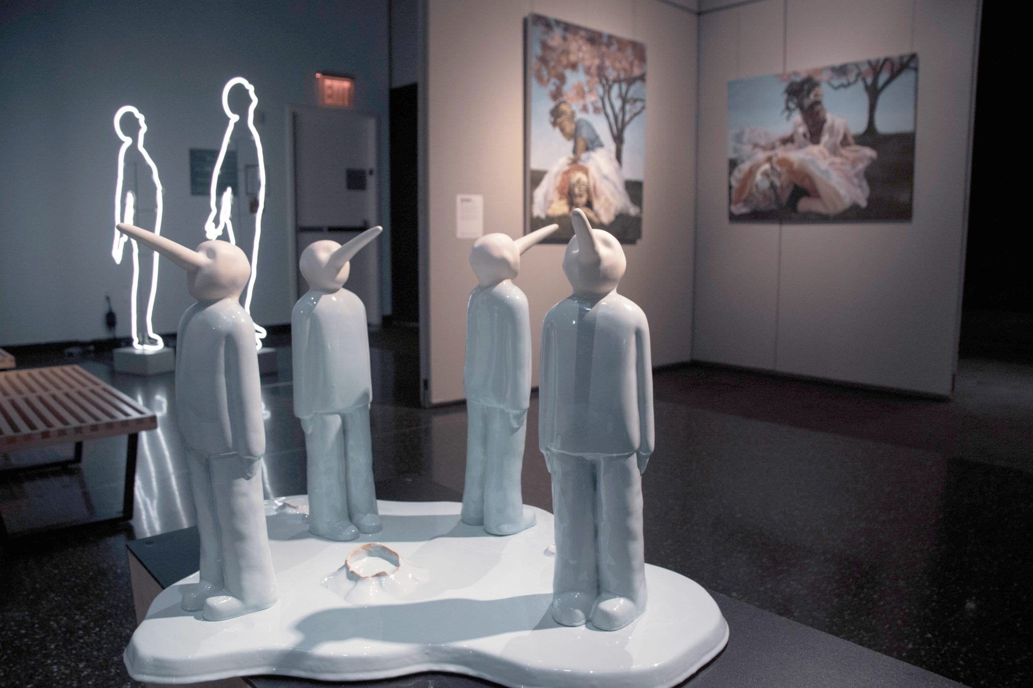 A group of sculptural figures stand on a platform with exaggerated pointed noses