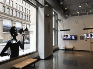 A gallery space, a large window on the left with a vinyl black cutout of a woman speaking into a megaphone, with monitors hanging in the righthand corner