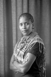 black and white portrait of a black woman against a faintly patterned background