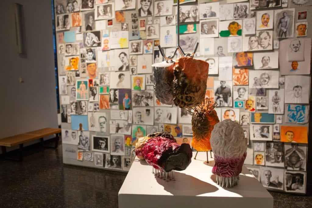 Sculptural heads stand on a pedestal in front of a wall of collaged drawings