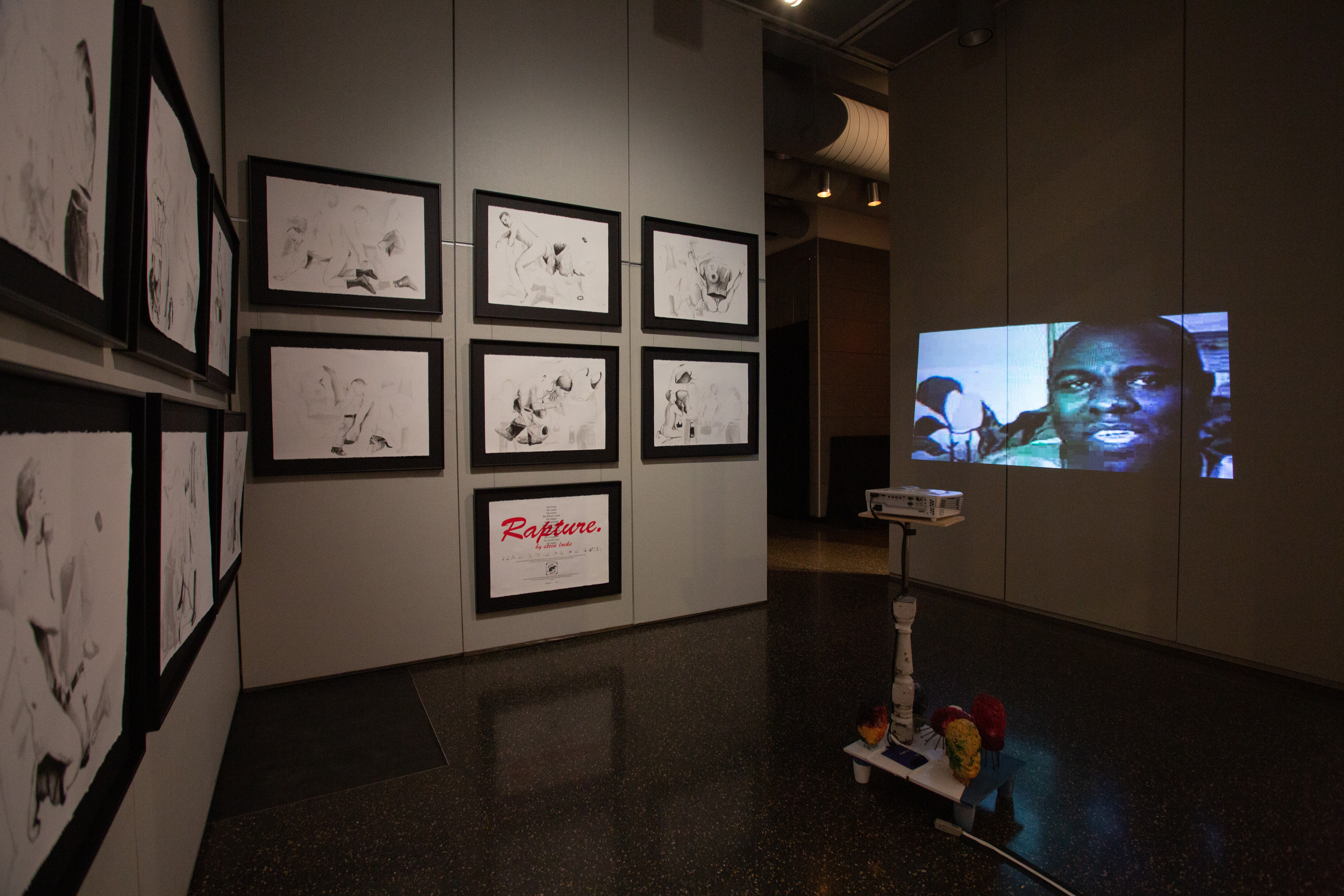 Gallery space with a grid of prints on the wall, a projector stands in the middle of the room and projects a video onto the rightmost wall